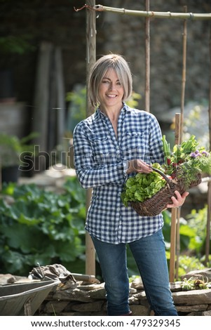 one summer day,a woman smiling, forty years old,standing in her garden on a stonewall, she's holding a basket in one's hand, in which is vegetables and flowers, there is a wheelbarrow near her