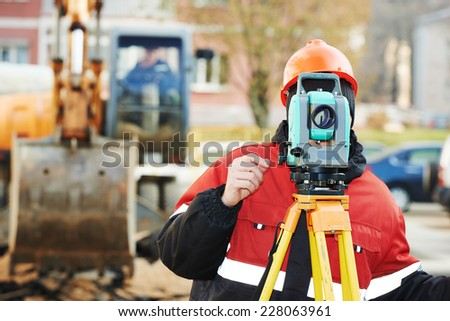 One surveyor worker working with theodolite transit equipment at road construction site outdoors - stock photo