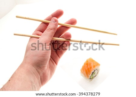 one sushi with hand and sticks on white background