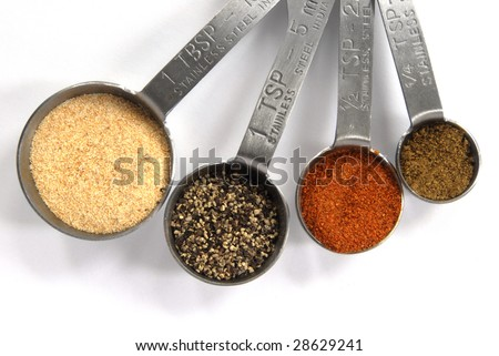 One Tablespoon, One Teaspoon, Half Teaspoon and Quarter Teaspoon measuring spoons filled with colorful spices isolated on a white background. - stock photo