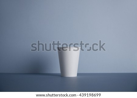 One take away white paper cup presented in center, isolated on gray - stock photo
