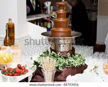 one tall 4 level chocolate fountain and various dunking items at a wedding reception - stock photo