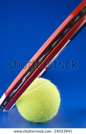 One tennis ball next to a tennis racket on a blue background. - stock photo