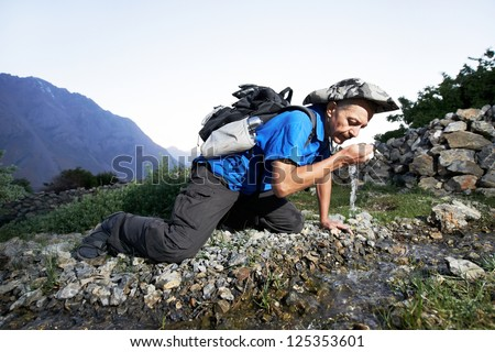 One thirsty tourist traveller hiker drinking pure water in India Himalayas mountains source