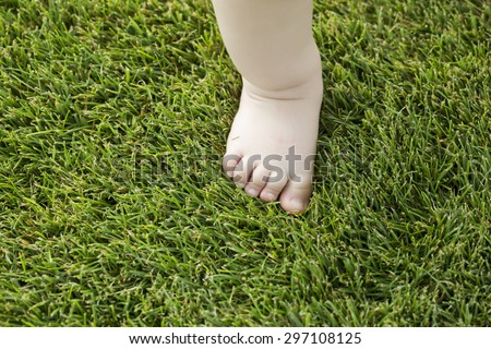 One tiny little bare baby foot of small child with soft skin making step on fresh green lush grass outdoor on natural background closeup, horizontal picture - stock photo