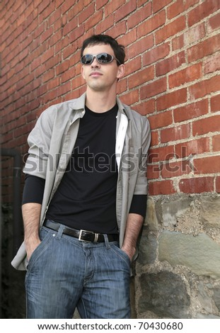 one twenties young man leaning on a brick wall outdoors in grungy setting