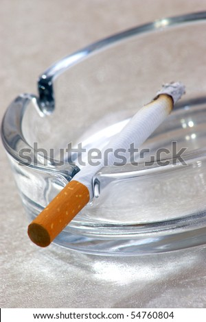 one unhealthy cigarette in a glass ashtray