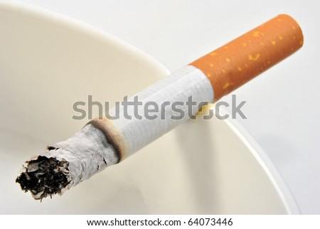 one unhealthy cigarette in a glass ashtray - stock photo