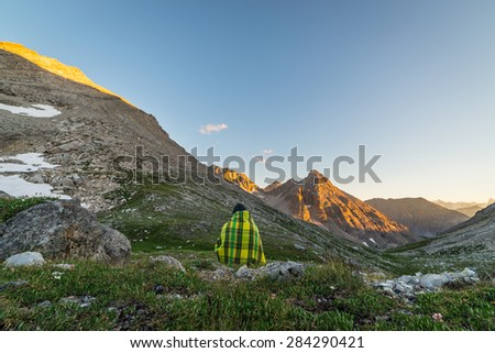 One unrecognizable person covered by blanket sitting and watching sunset high up in the Alps. Wide angle view with flowering meadow in the foreground and glowing mountain peaks in the background. - stock photo
