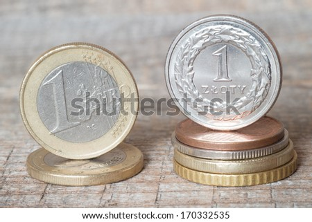 One uro coin and one zloty coin on wood table - stock photo