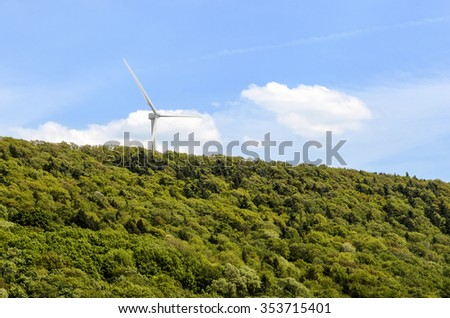 One Visible Wind Turbine in Rural Treed Hill Area - stock photo