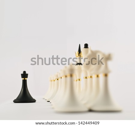 One voice against many concept as black chess pawn figure opposite to the white ones composition - stock photo