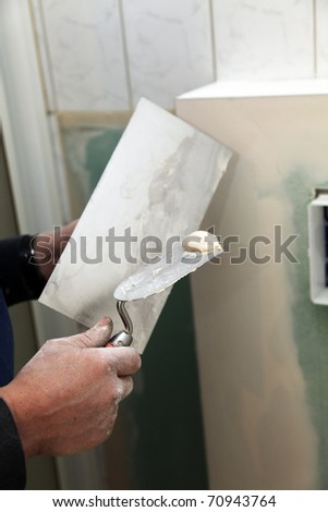 One wall is plastered. A trowel with plaster is held in one hand. - stock photo