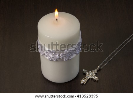 One white candle lit with pendant crystal cross on wood background