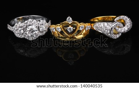 One white diamond ring and two golden diamond rings on black background