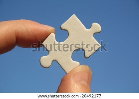 One white jigsaw puzzle piece in human fingers