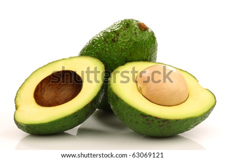 one whole and one cut avocado on a white background - stock photo