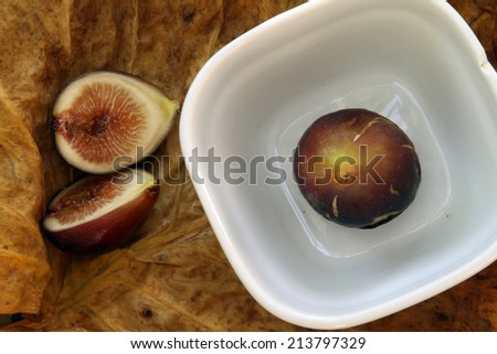 one whole and one cut in half purple figs in a white bowl on a background of golden yellow leaves