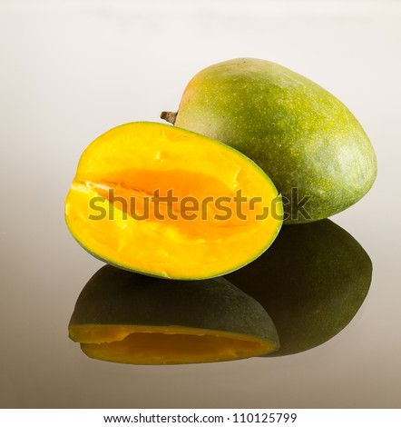 One whole and one cut mango on reflecting glass surface with gradient - stock photo