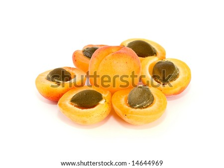 One whole and six apricot halves with kernels lying in form of flower isolated on the white background