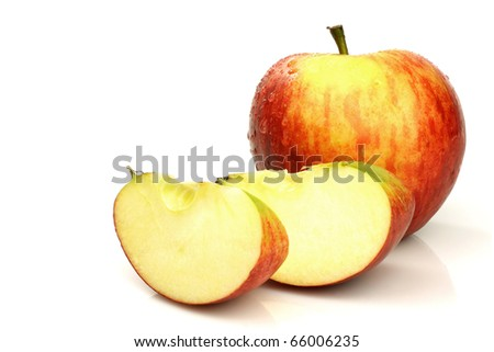 one whole apple and some pieces on a white background - stock photo