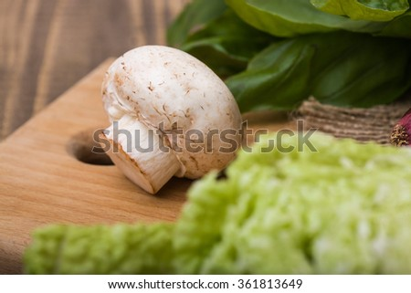 One whole raw white champignon with chinese cabbage and topherbs on wooden cutting board, horizontal photo