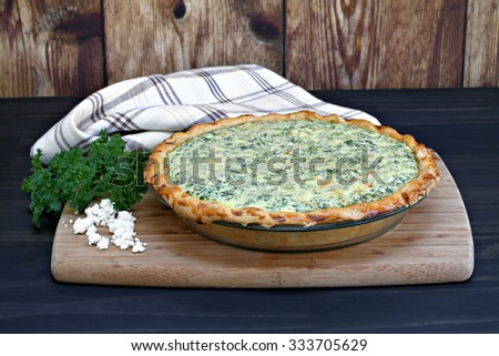 One whole spinach and feta cheese quiche on a cutting board - stock photo