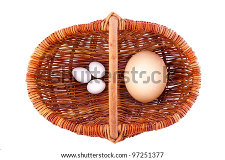 one wicker  basket with ostrich egg and three chicken eggs - stock photo