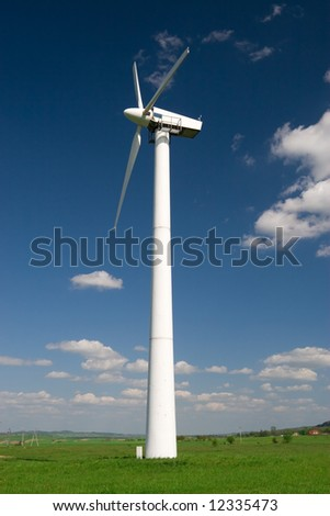One wind turbine against blue sky with white clouds - stock photo