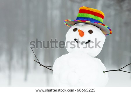 one winter snowman with coloured top hat standing in forest outdoors - stock photo