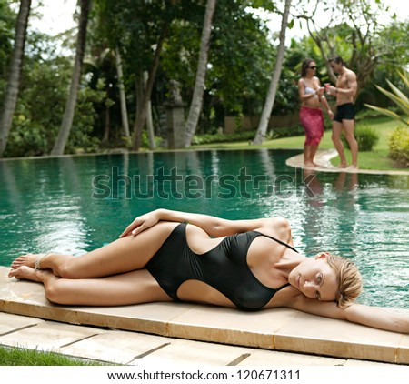 One woman and a couple lounging and relaxing by the edge of a swimming pool in a tropical destination hotel spa garden while on vacations. - stock photo