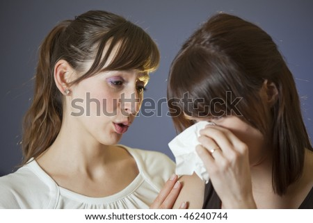 one woman crying with handkerchief - another comforting her