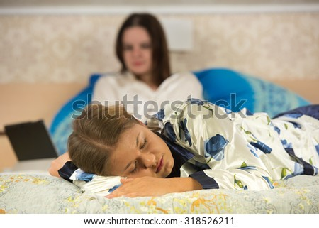 One woman in the front sleeping, another one on the back works with tablet pc - stock photo