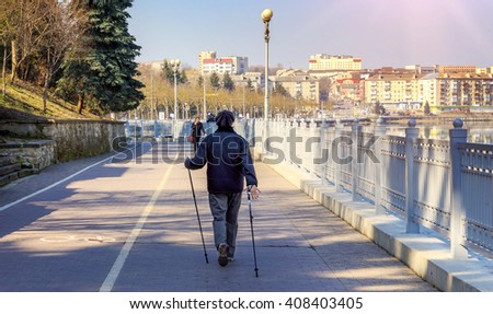 one woman in the park - Nordic walking. health concept. the lake in a city park. beautiful sunny morning. - stock photo