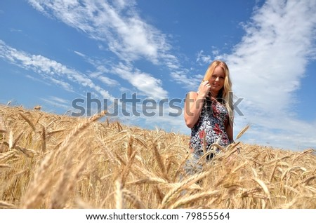 One woman in the spacious field of the wheat against the background of the blue sky.