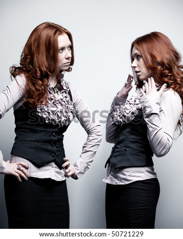 One woman in two roles. On gray wall background. - stock photo