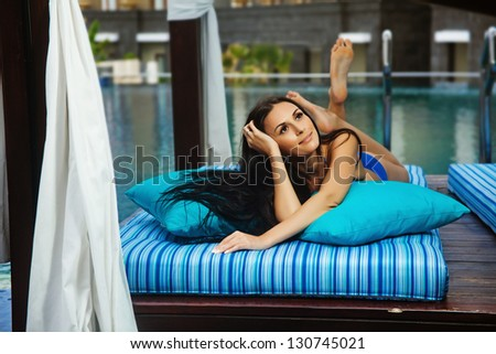 one woman sitting near swimming pool in hotel, bali - stock photo