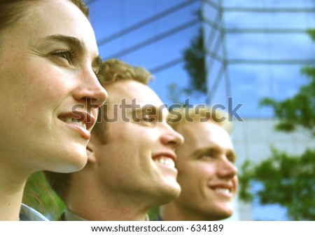 one woman two males profile view in a row smiling with business building exterior - stock photo