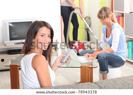 one woman watching tv, a woman doing computer and someone vacuuming