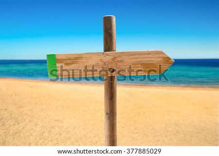 one wooden signpost in the meadow with copyspace on the beach - stock photo