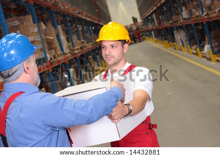 one worker in uniform receiving box from another  in warehouse - stock photo
