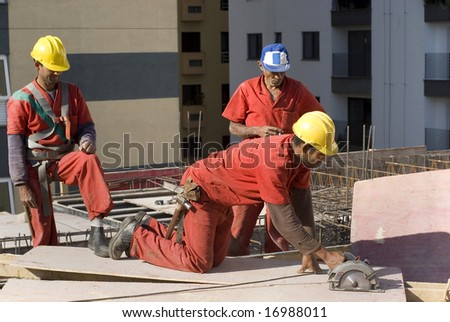 One worker is making a cut a on a sheet board with a circular saw.  Their are two other workers standing behind him.  Horizontally framed shot. - stock photo
