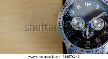 One wristwatch on wooden background - stock photo