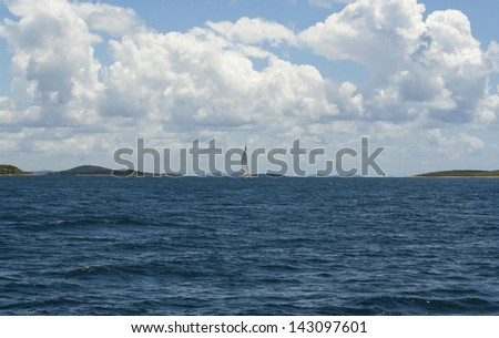 one yacht with islands and clouds on horizon