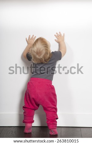 one year age blonde lovely cute caucasian white baby grey shirt pink trousers and shocks standing indoor on brown floor against white wall looking up copy space - stock photo
