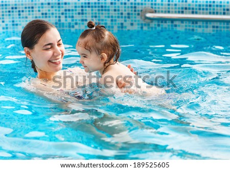 One year baby girl at her first swimming lesson with mother in the pool
