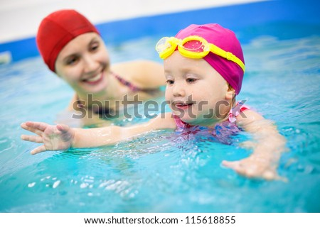 One year  baby girl at his first swimming lesson wiht mother - stock photo