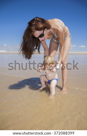 one year baby swimsuit touching water in woman mother hands at beach next to Conil Cadiz Spain - stock photo