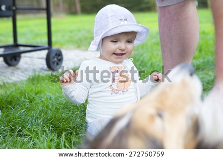 one year happy girl with her  doggy portrait lying on lawn - stock photo
