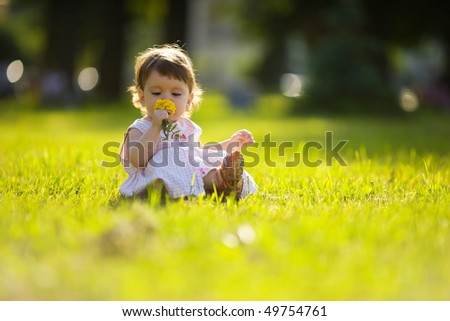 One year little girl sniffing flower summer park outdoors - stock photo